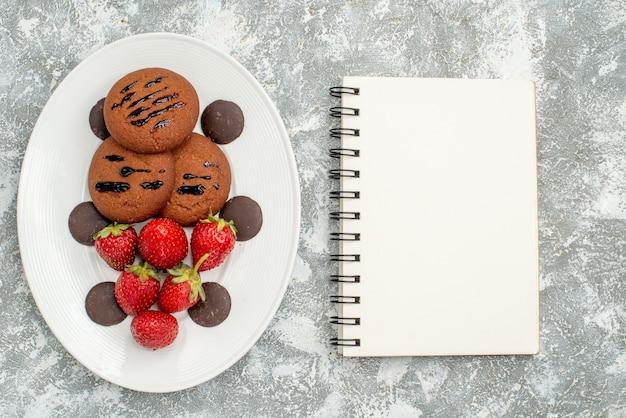 Draufsicht schokoladenkekse erdbeeren und runde pralinen auf dem weißen ovalen teller links und einem notizbuch auf der rechten seite des grauweißen grundes