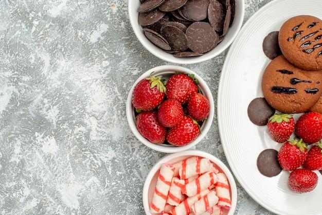 Draufsicht schokoladenkekse erdbeeren und runde pralinen auf dem weißen ovalen teller und schalen mit süßigkeiten erdbeerpralinen auf dem grauweißen grund
