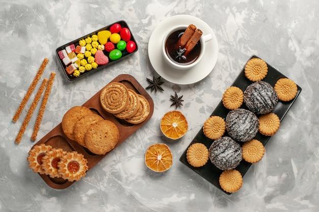 Draufsicht schokoladenkuchen mit keksen bonbons und tasse tee auf weißer oberfläche