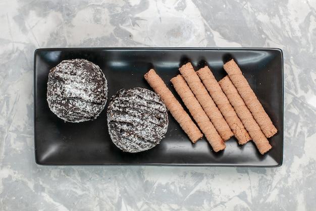 Draufsicht schokoladenkuchen mit süßen pfeifenplätzchen innerhalb der schwarzen platte auf weißer oberfläche