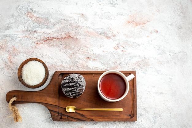 Draufsicht schokoladenkuchen mit tasse tee auf weißem schreibtisch schokoladenkuchen kekszucker süßer keks