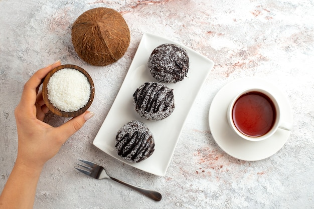 Draufsicht schokoladenkuchen mit tasse tee und kokosnuss auf weißer oberfläche schokoladenkuchen kekszucker süßer keks