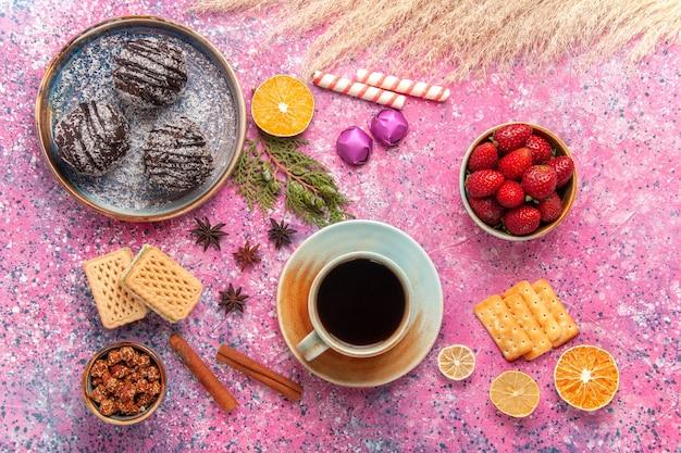 Draufsicht schokoladenkuchen mit waffeln und tasse tee auf rosa