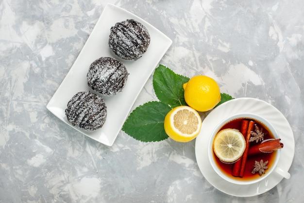 Draufsicht schokoladenkuchen mit zitrone und tasse tee auf weißer oberfläche