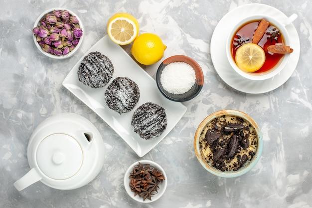 Draufsicht schokoladenkuchen mit zitrone und tee auf weißer oberfläche