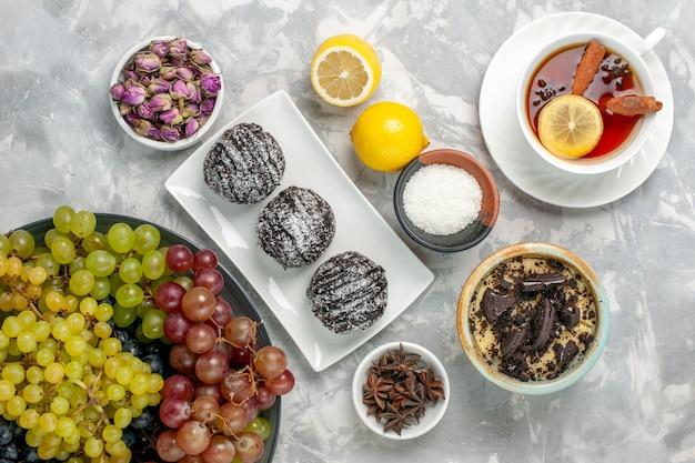 Draufsicht schokoladenkuchen mit zitronentrauben und tee auf weißer oberfläche