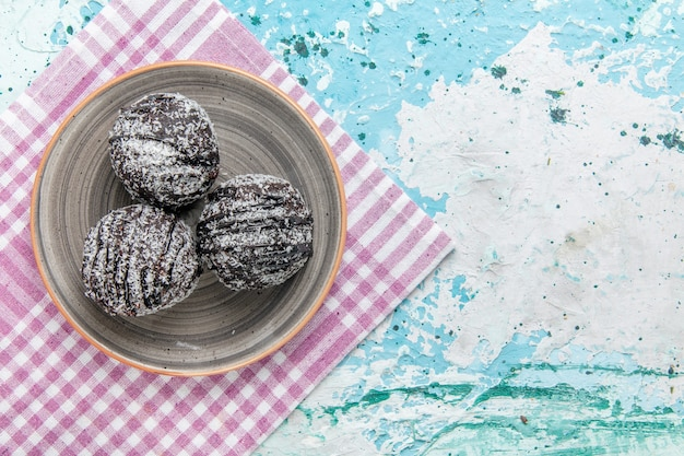 Draufsicht schokoladenkuchen mit zuckerguss und zuckerpulver auf hellblauer hintergrundkuchenschokoladenkekszuckersüße farbe