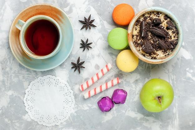 Draufsicht schokoladenplätzchen-dessert mit französischen macarons-bonbons und tee auf hellweißem schreibtischplätzchen-süßem backzuckerkuchenkeks