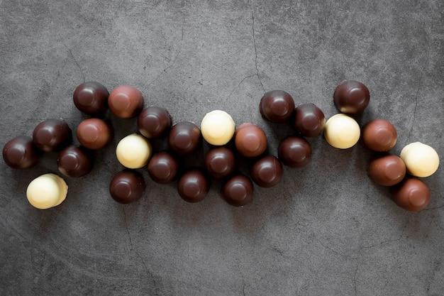 Draufsicht-schokoladensortiment auf dunklem hintergrund