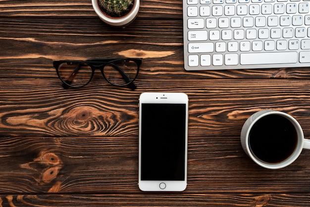 Draufsicht schreibtisch mit einer tasse kaffee und smartphone und gläsern