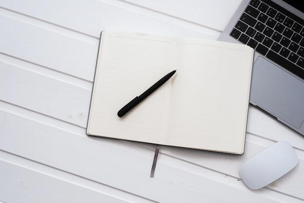 Draufsicht-schreibtisch mit laptop, notizbüchern und kaffeetasse auf weißem farbhintergrund. bürotisch mit leerem notizbuch und laptop