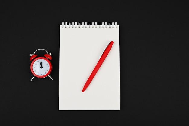 Draufsicht-schreibtisch über offenem notizbuch mit bleistift und rotem wecker auf schwarzem hintergrund.