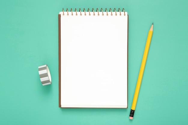 Draufsicht schreibtischanordnung mit leerem notizblock auf blauem hintergrund