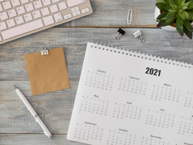 Draufsicht schreibtischkalender mit saftiger pflanze