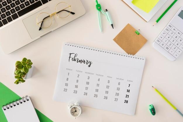Draufsicht schreibtischkalender und niedliche innenpflanze