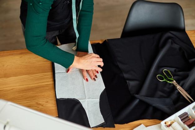Draufsicht schritt für schritt, damenschneiderin, die schnittmuster herstellt, reifer schneider, der mit schnittmustern in atelier, textilindustrie, hobby, arbeitsbereich arbeitet. kreationsprozess diy, arbeitsplatz der näherin