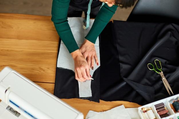Draufsicht schritt für schritt, schneiderin, die schnittmuster macht, reifer schneider, der mit schnittmuster im atelier, in der textilindustrie, im hobby, im arbeitsbereich arbeitet.