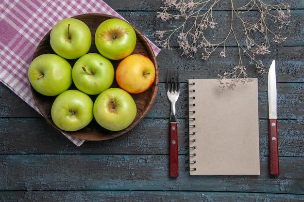 Draufsicht schüssel mit äpfeln schüssel mit sieben grün-gelben äpfeln auf karierter tischdecke neben zweigen gabelmesser und grauem notizbuch