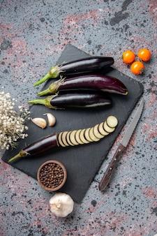 Draufsicht schwarze auberginen auf schneidebrett blaue oberfläche essen abendessen mittagessen mahlzeit baum wachsen reife junge farbe