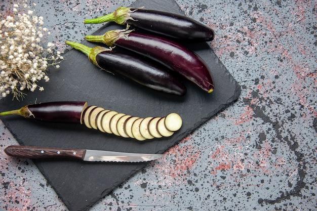 Draufsicht schwarze auberginen auf schneidebrett blaue oberfläche essen abendessen mittagessen salat farbe mahlzeit baum wachsen reif jung