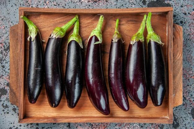 Draufsicht schwarze auberginen im schneidebrett auf heller oberfläche lebensmittelfarbe reife mahlzeit frischer salat gemüsedinner