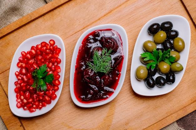 Draufsicht schwarze und grüne oliven mit granatapfelsauce und geschältem granatapfel