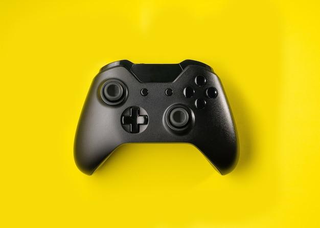 Draufsicht schwarzer controller auf gelbem raum