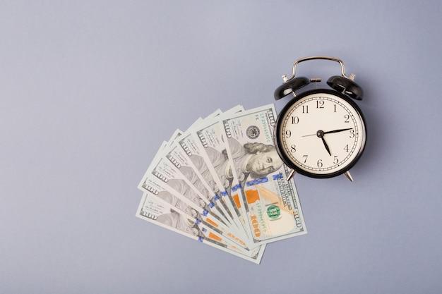 Draufsicht schwarzer metallwecker auf einem stapel von dollarbanknoten. flach legen