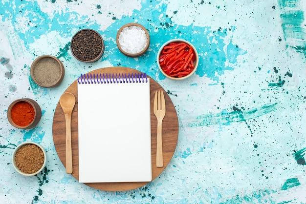 Draufsicht seasonigns und paprika mit notizblock auf dem hellblauen hintergrundpfefferproduktgemüsefarbfoto