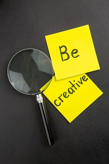 Draufsicht sei kreativ, geschrieben auf haftnotizen lupa an dunkler wand