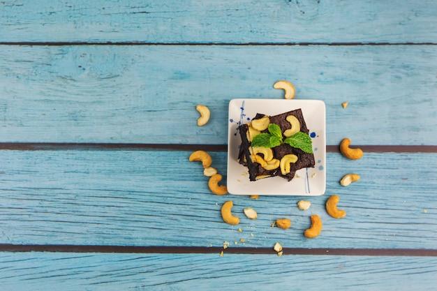 Draufsicht selbst gemachter schokoladen-brownie auf einem blauen holzhintergrund