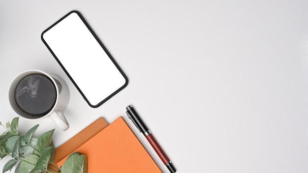 Draufsicht smartphone, kaffeetasse und notebook auf weißem schreibtisch.