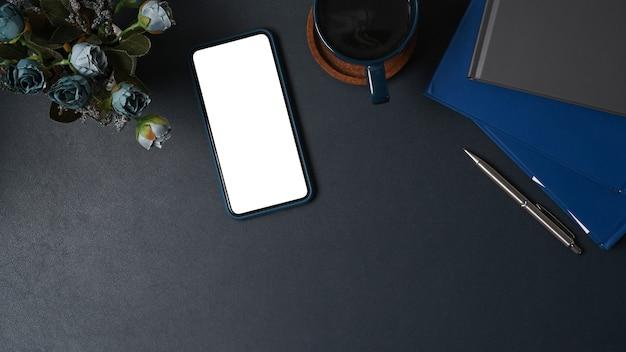 Draufsicht-smartphone mit leerem bildschirm auf schwarzem leder.