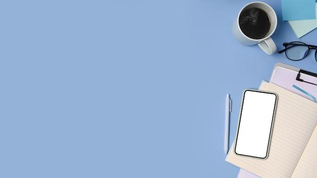 Draufsicht-smartphone mit leerem bildschirm, kaffeetasse und notebook auf blauem hintergrund.