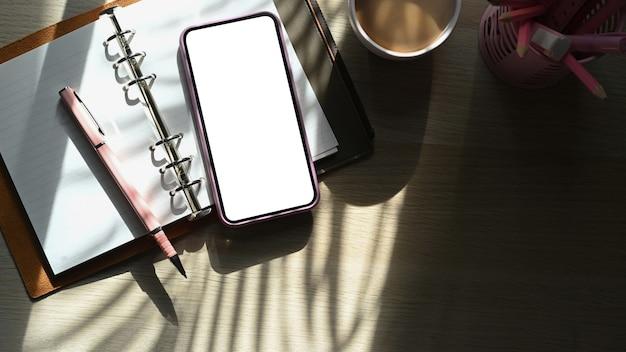 Draufsicht smartphone, notebook und kaffeetasse auf holztisch.