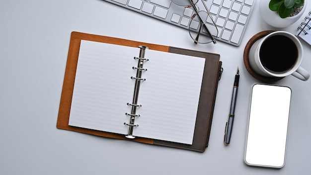 Draufsicht smartphone, notebook und kaffeetasse auf weißem schreibtisch.