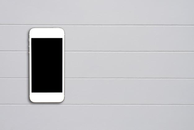 Draufsicht smartphonespott herauf schablone mit schwarzem schirm auf zementtabelle mit copyspace.