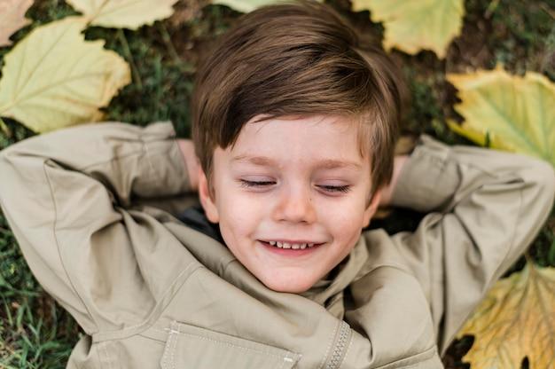 Draufsicht smiley kleiner junge, der auf dem gras bleibt
