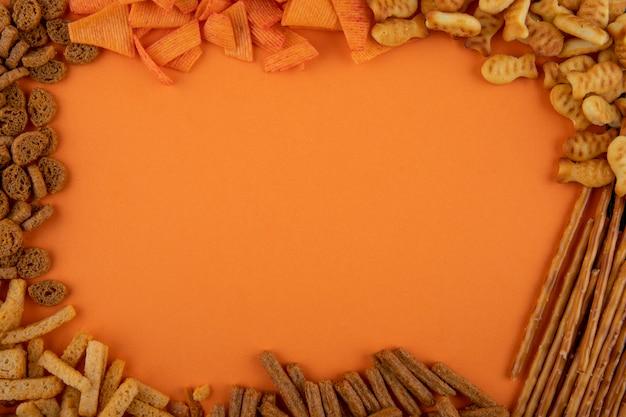 Draufsicht-snacks mit paprika-chips-cracker-sticks kopieren hartes chuck und mini-brezel auf orangefarbenem hintergrund