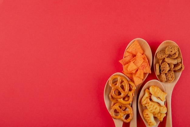 Draufsicht snacks paprika-chips hartfutter mini brezel und fischcracker auf der linken seite mit kopierraum auf rotem hintergrund