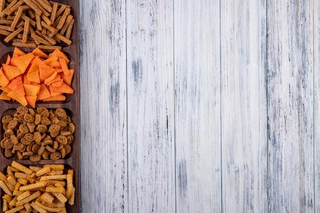 Draufsicht snacks paprika-chips und hartes futter auf der linken seite mit kopienraum auf weißem hölzernem hintergrund