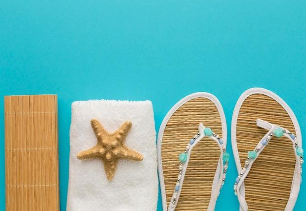 Draufsicht sommerhausschuhe mit handtuch und seestern
