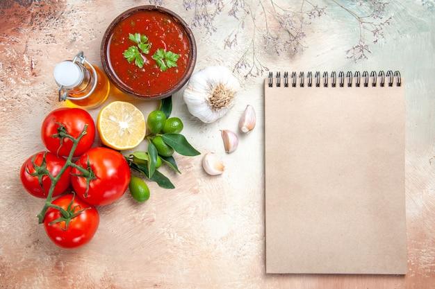 Draufsicht soße flasche öl tomaten mit stiel zitronensauce knoblauchcreme notizbuch