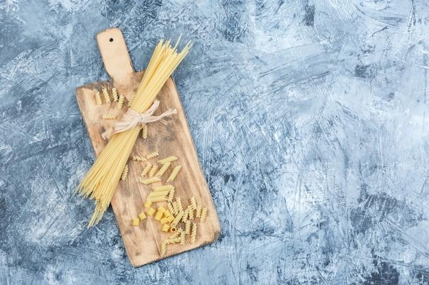 Draufsicht-spaghetti auf grauem gips und schneidebretthintergrund. horizontal