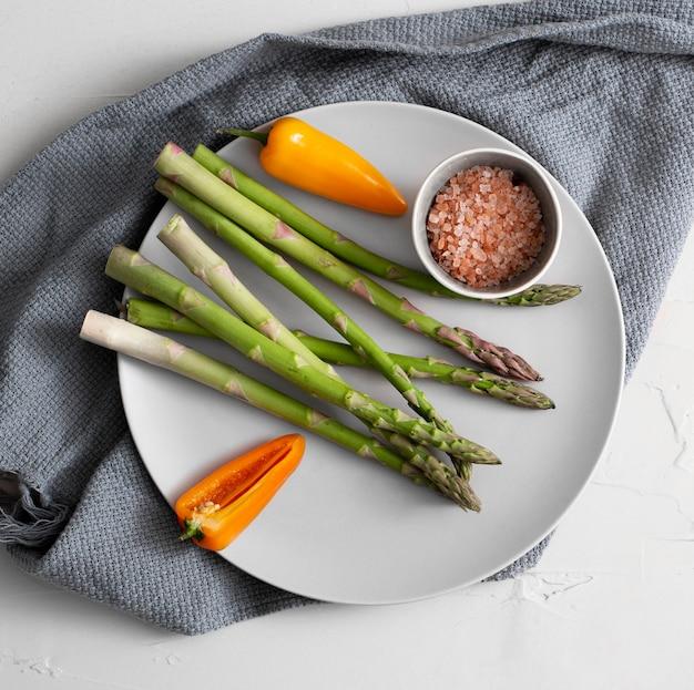 Draufsicht spargel, pfeffer und himalaya-salz auf teller mit küchentuch