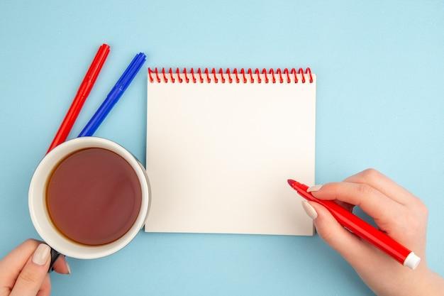 Draufsicht spiralnotizbuch tasse tee und roter marker in weiblichen händen rote und blaue marker auf blau