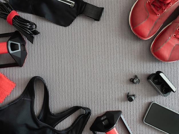 Draufsicht sportbekleidungskonzept mit gym outfit, laufschuhen, smartphone, echten kabellosen ohrhörern und sportlaufzubehör auf yogamattenhintergrund.