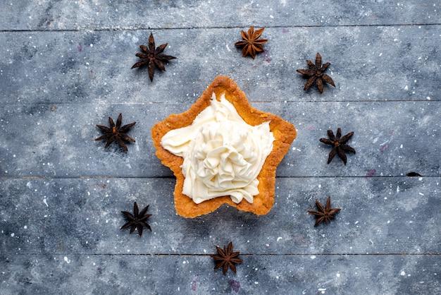 Draufsicht sternförmiger kuchen mit sahne auf dem leichten schreibtischkuchenkeks süßer zucker backen sahne