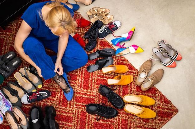 Draufsicht stilvolle blonde frau posiert bei der auswahl von schuhen auf dem boden in der boutique beim einkaufen?