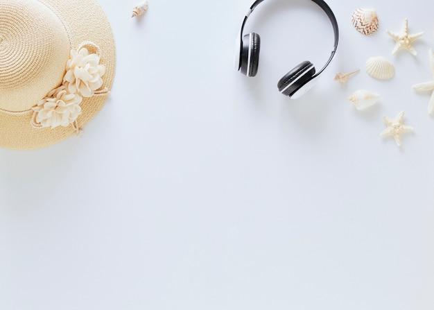 Draufsicht strohhüte mit gläsern und musikkopfhörerferiensommer